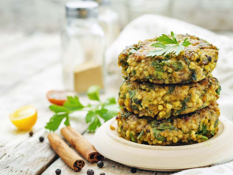 Spicy vegan curry burgers with millet, chickpeas and herbs.