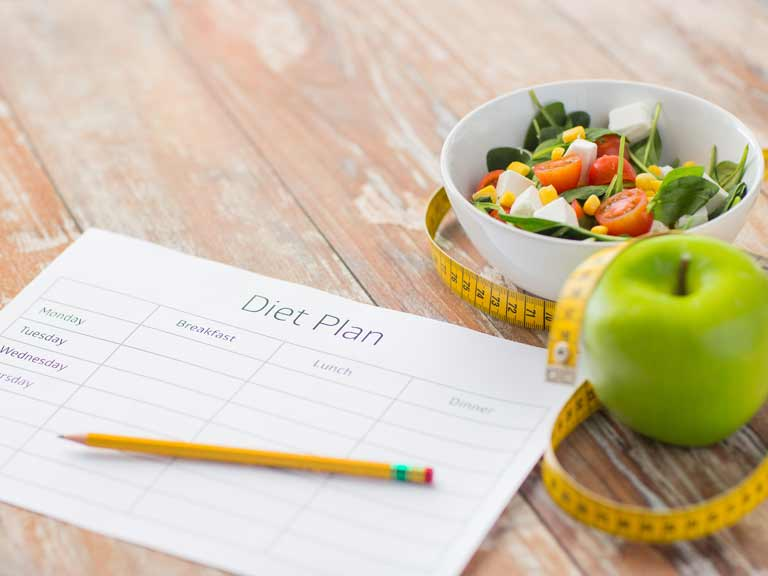 Weight loss tools, including diet diary, low calorie food and tape measure