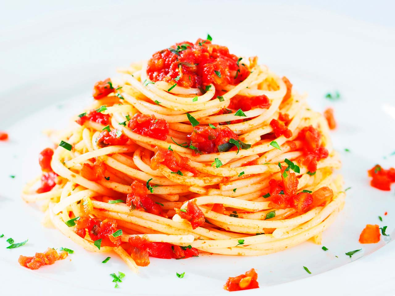 Spaghetti with tomatoes on a white plate