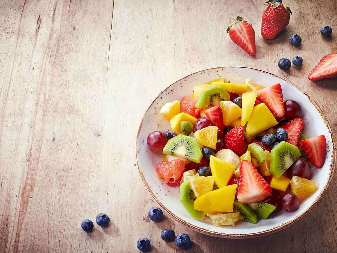 Bowl of healthy fruit on a wooden background