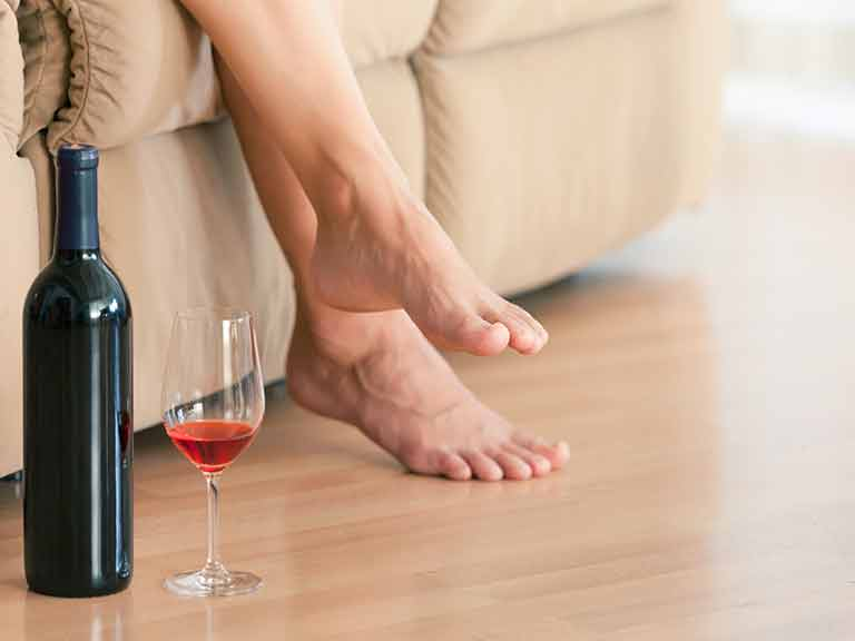 Woman relaxing on sofa with glass of wine