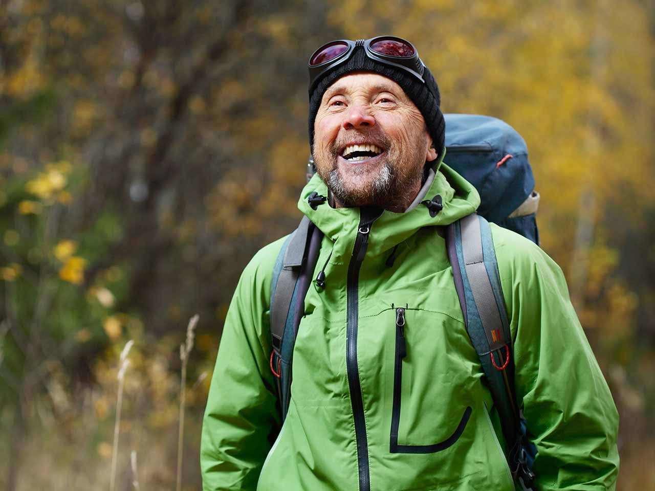 Mature man hiking with backpack and laughing