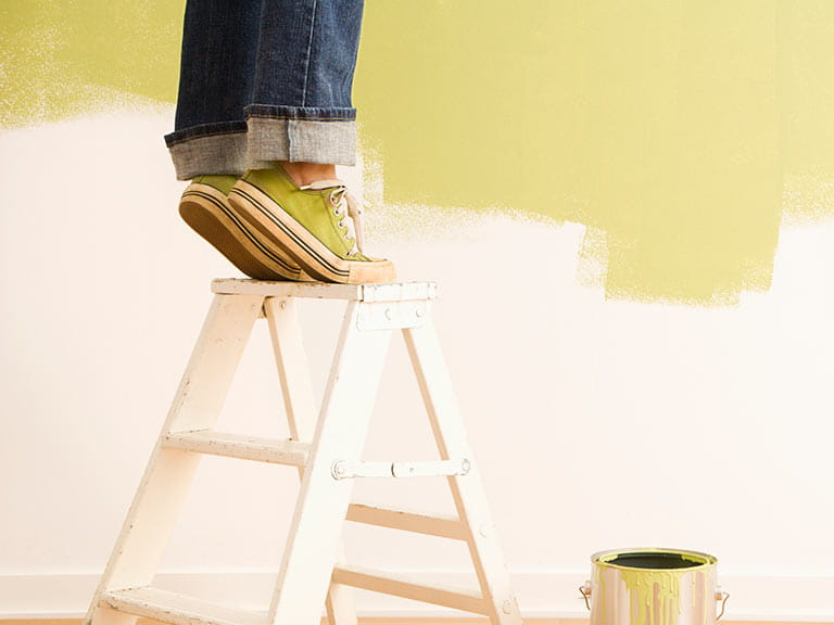 Woman standing on tiptoes on ladder decorating