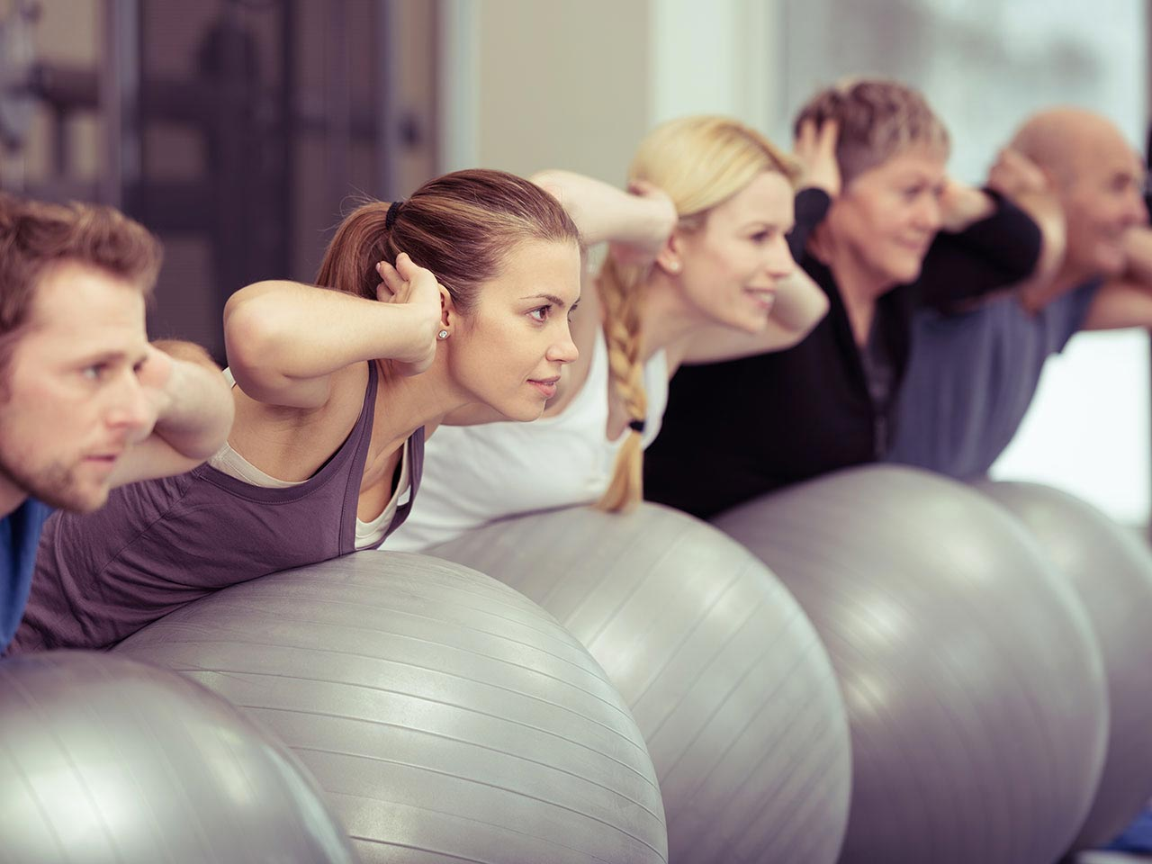Group of people in gym using pilates balls