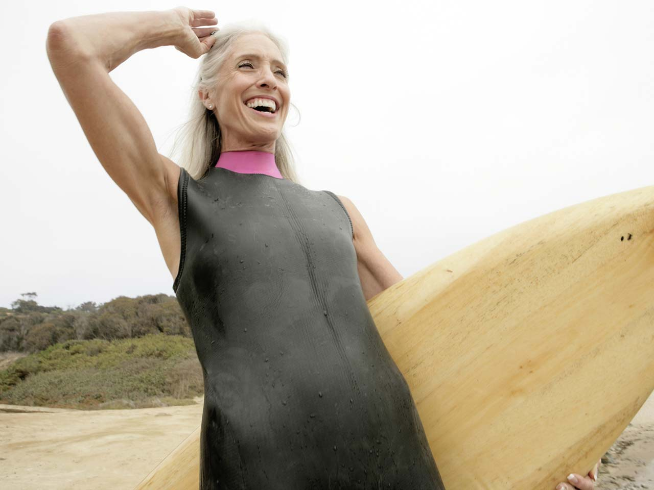 Older woman surfing to stay fit