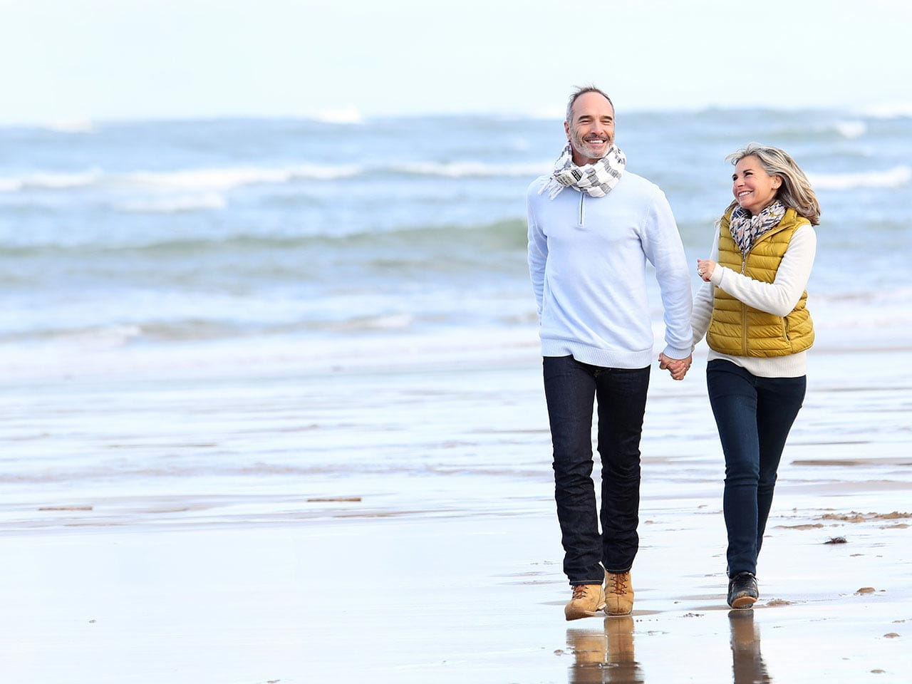 Happy mature couple walking on the beach in winter