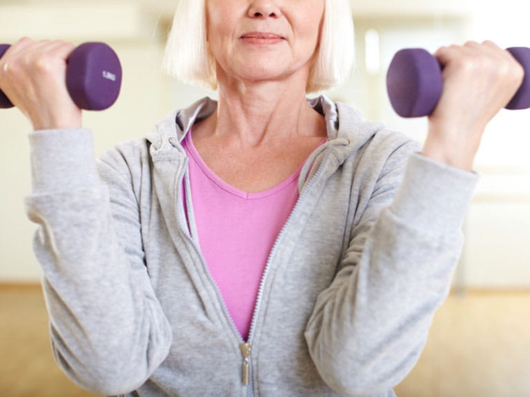 Woman lifting small weights to prevent muscle loss