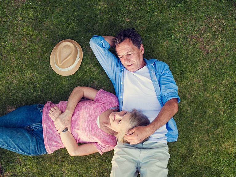 Mature couple lying on the grass and talking