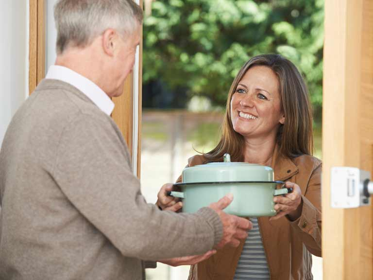 Woman bringing a home-cooked dish to a neighbour.