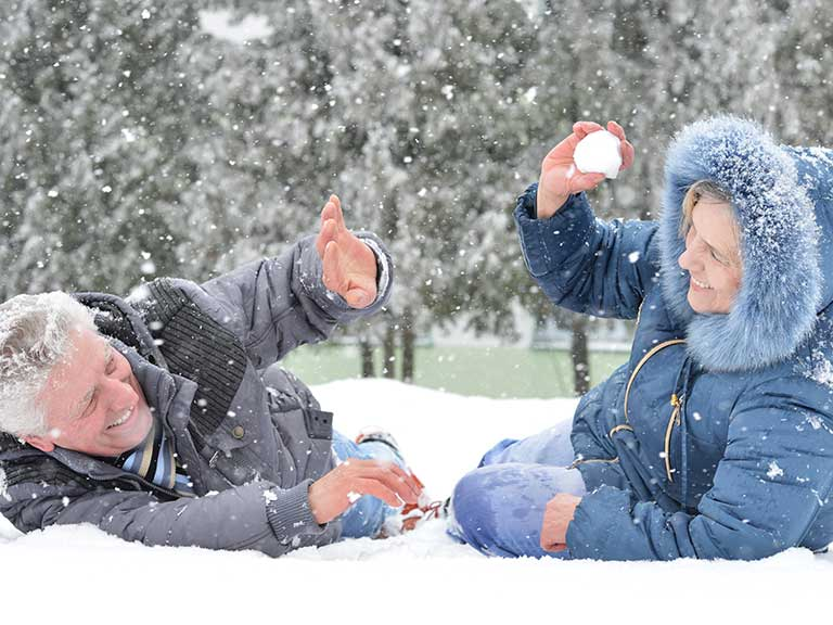 Senior couple having snowball fight and laughing