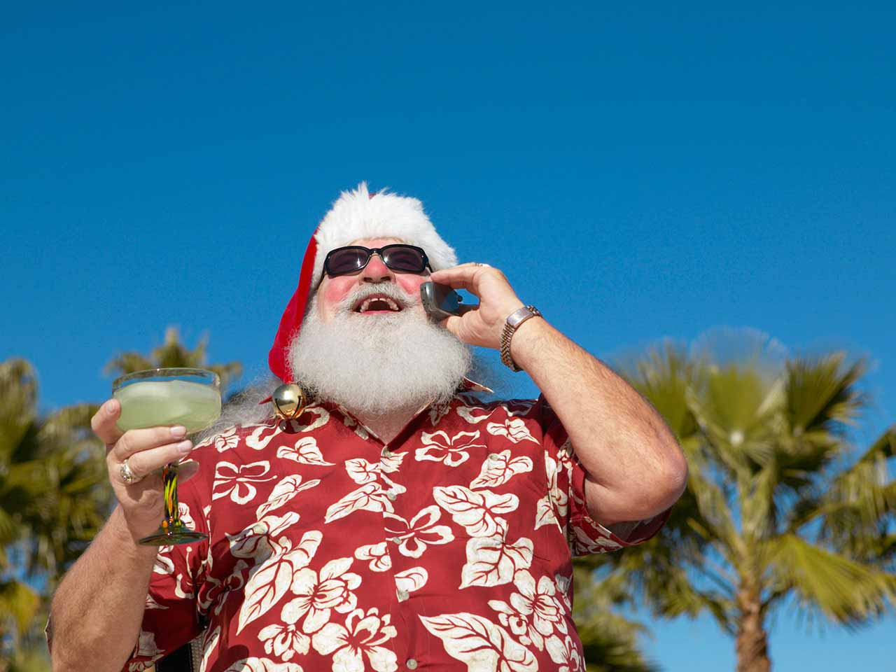 Man dressed as Father Christmas drinking a cocktail in the sun