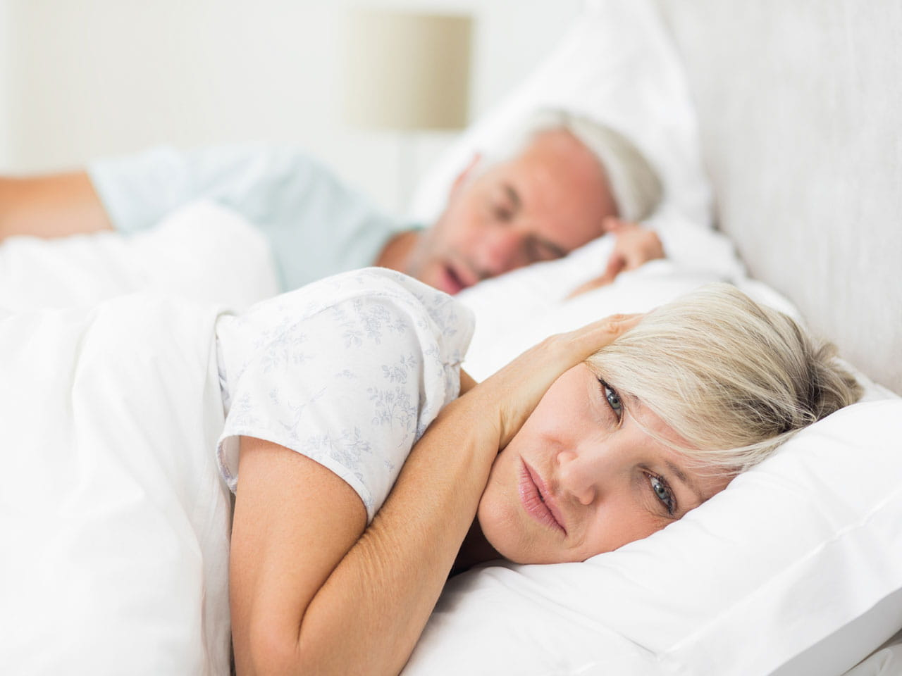 Mature couple in bed with man snoring and woman awake