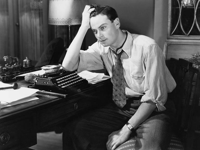 Retro image of a man sitting with typewriter looking frustrated