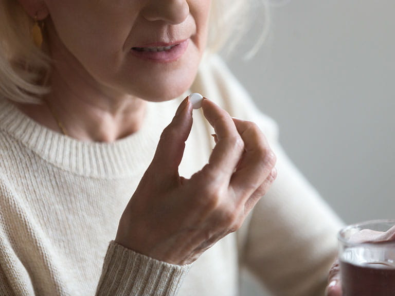 An older woman takes anti-depressants to combat her depression