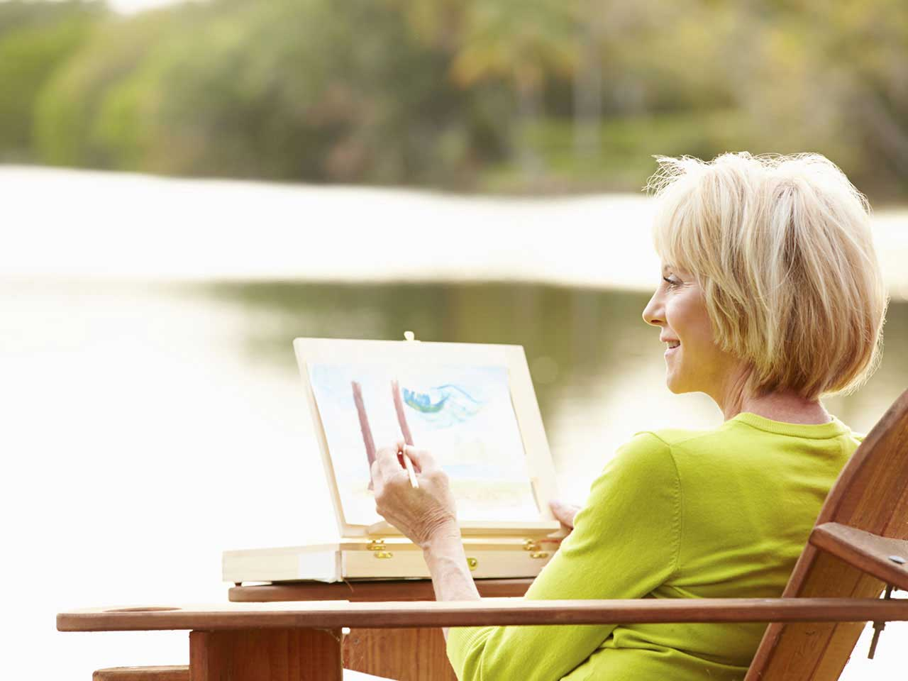 Mature lady sketching by a lake