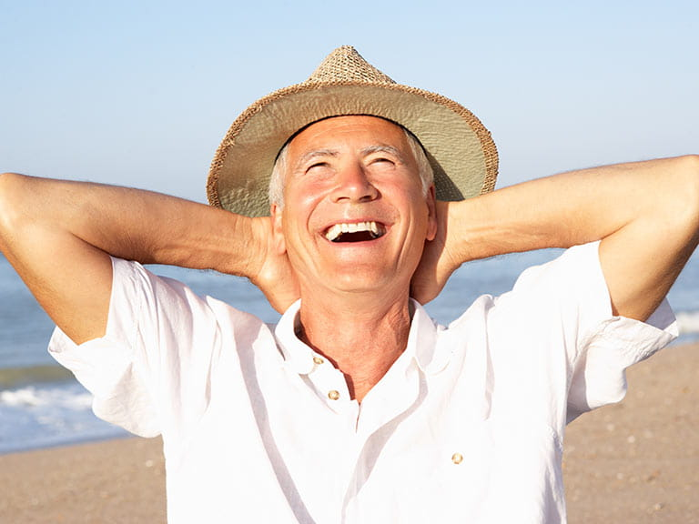Senior man laughing on the beach