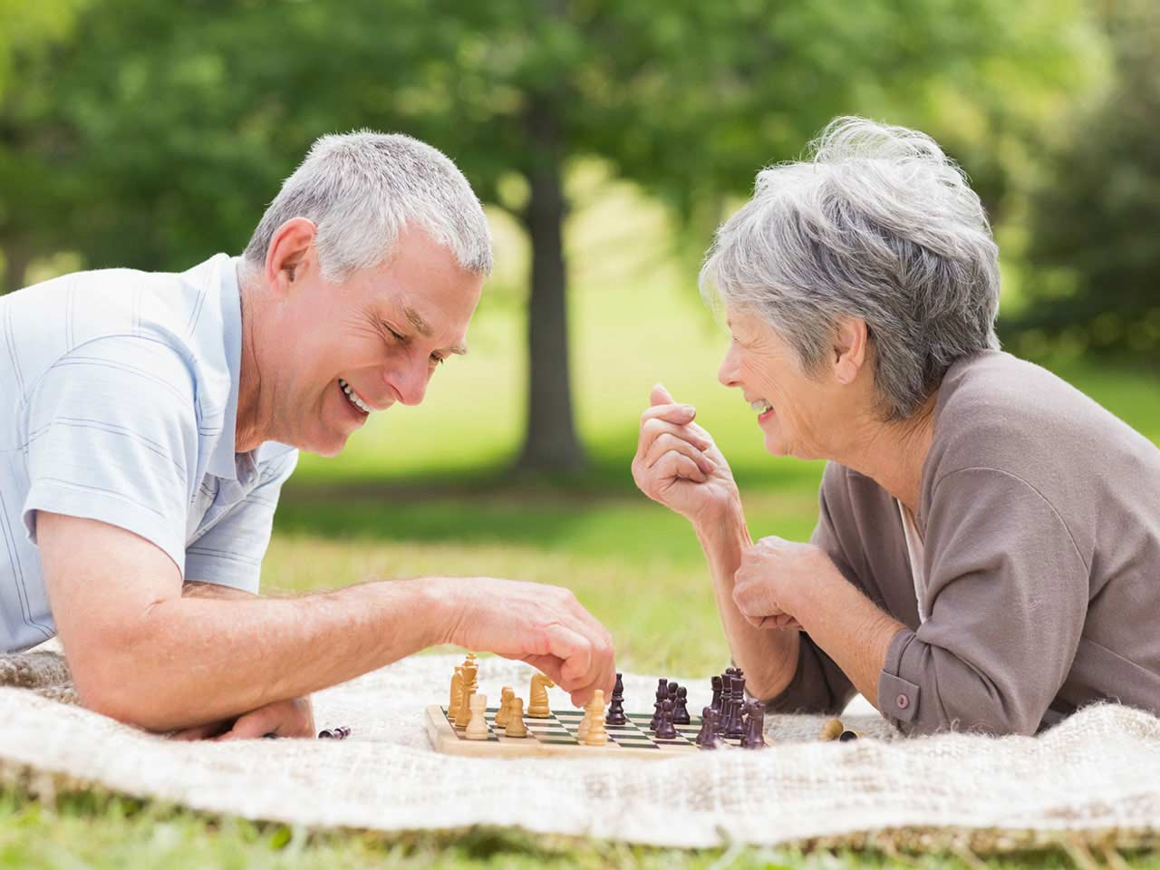 Mature couple laughing and playing chess in the park
