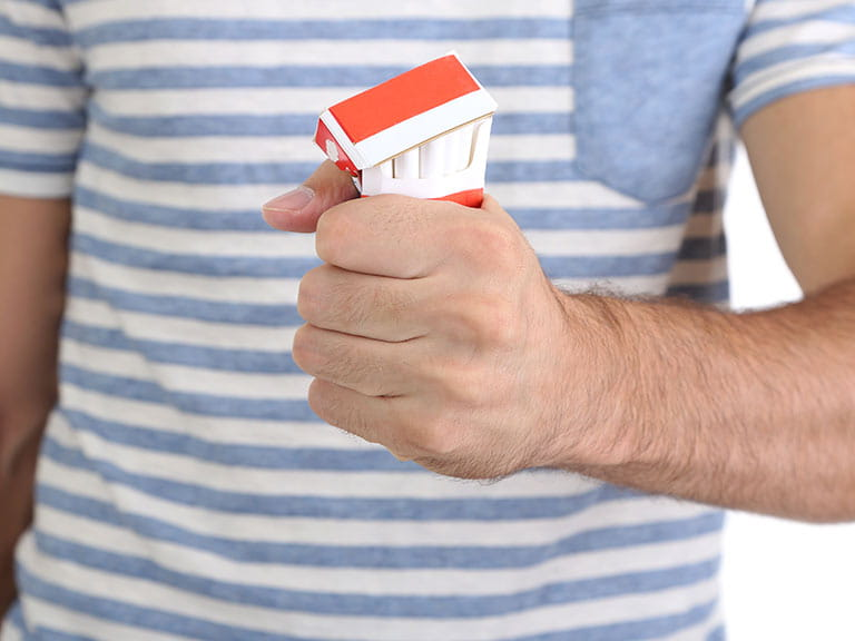Man's hand crushing cigarette packet