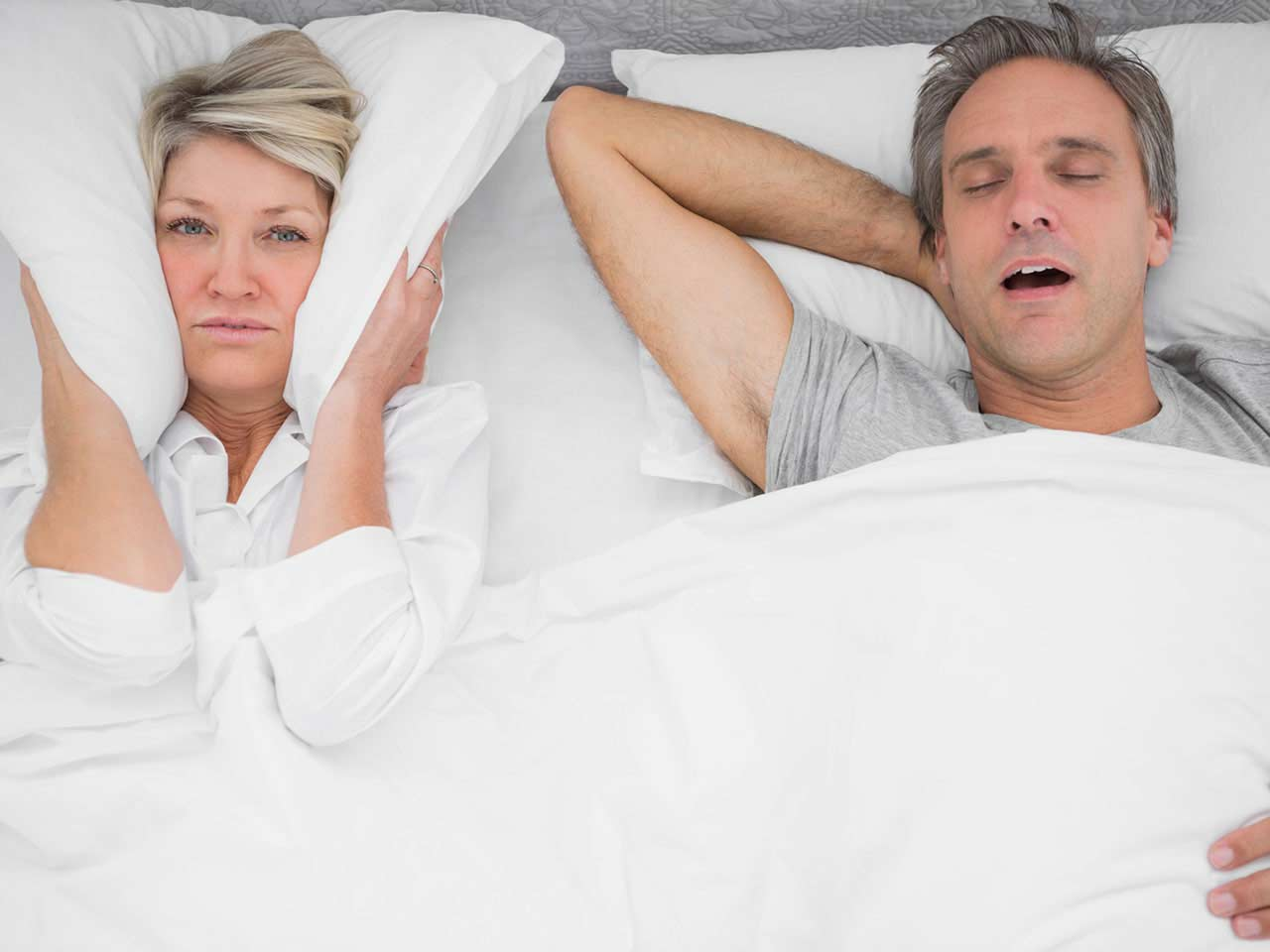 Mature couple in bed with the man snoring