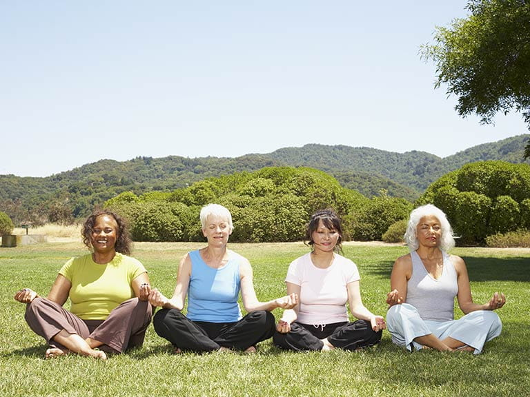 Senior women meditating in the park