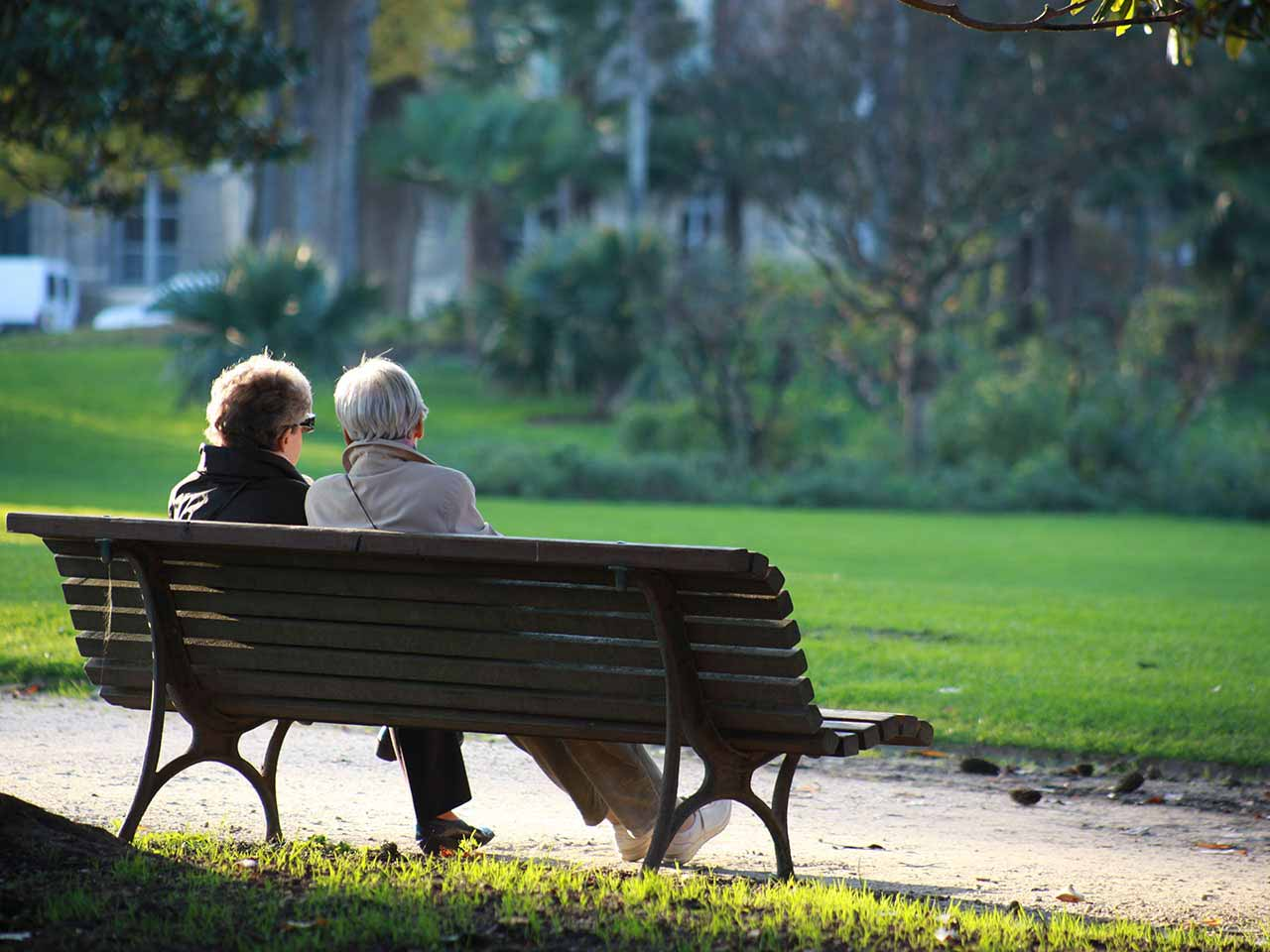Two mature women sitting on park bench