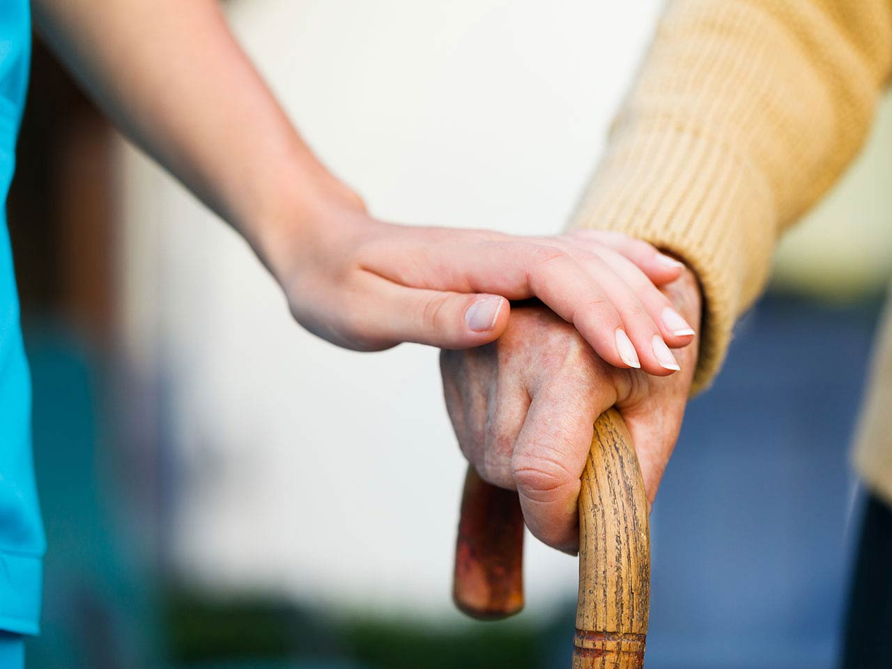 Nurse holding senior man's hand on walking stick