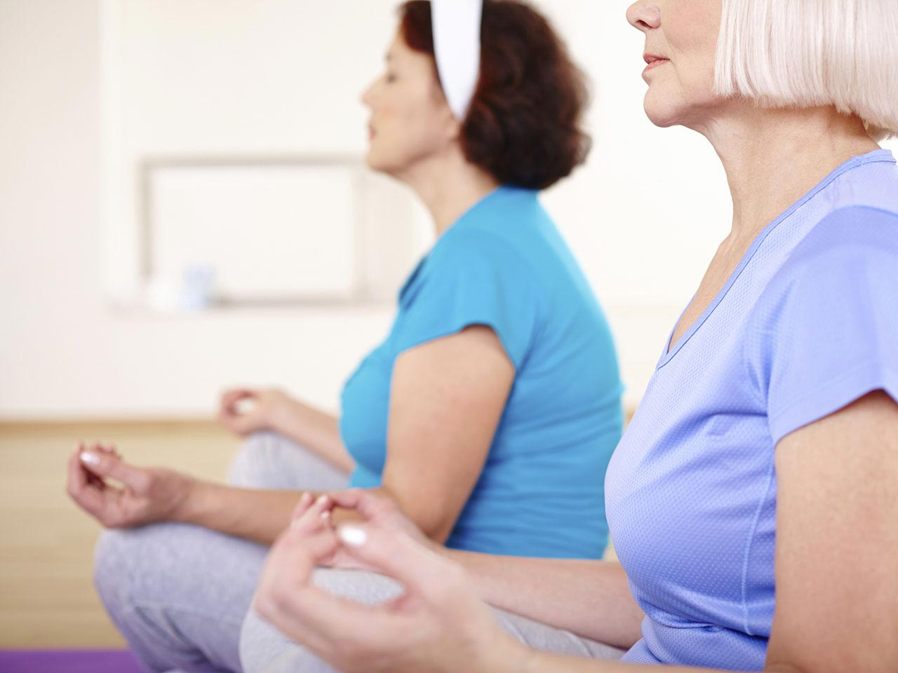 Senior ladies practising yoga, a common way to cope with hot flushes