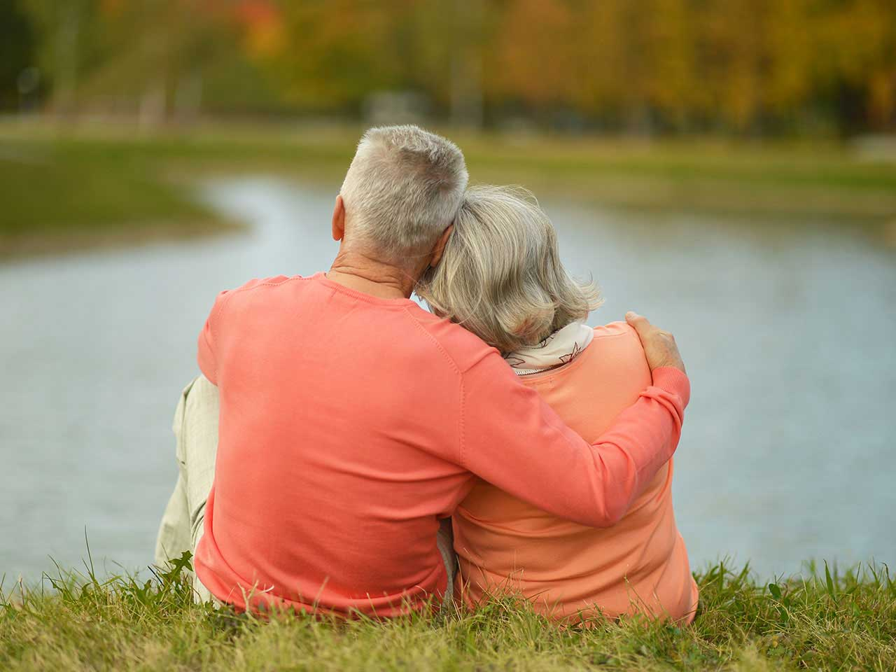 Mature couple looking thoughtful by a lake