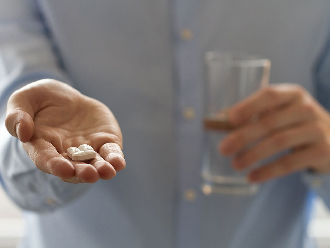 Man holding out his hand with painkillers