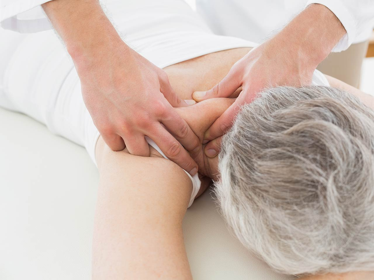 Senior receiving massage for neck pain
