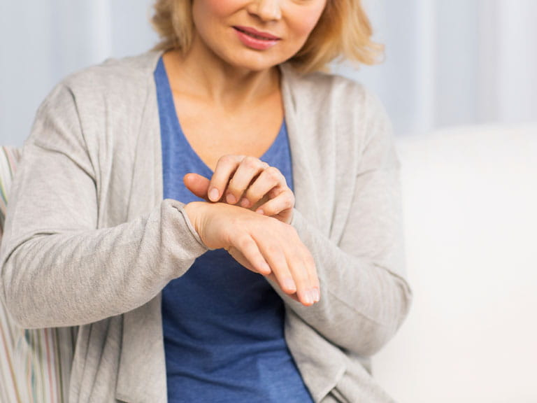 Mature woman scratching hand