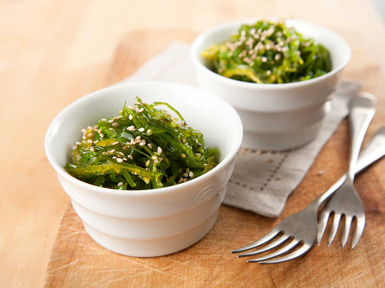 Two bowls of seaweed with sesame seeds