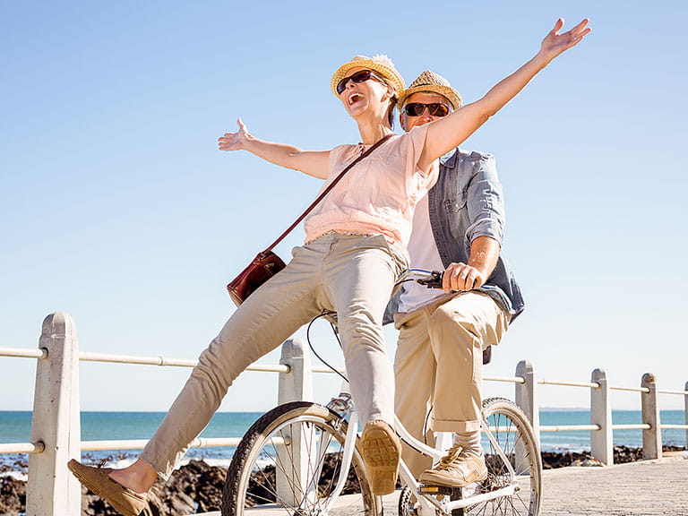 Mature couple riding a bike together in the sun