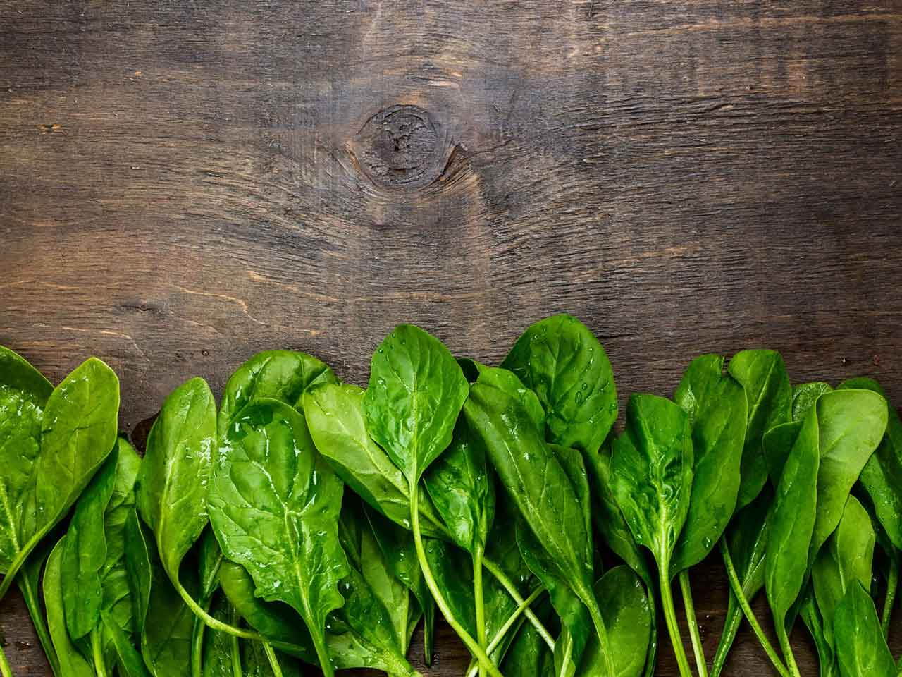Folic acid rich spinach on a wooden board