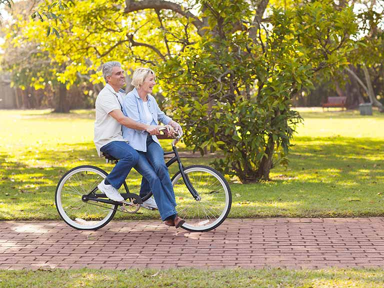 Mature couple riding on a bike outdoors having fun