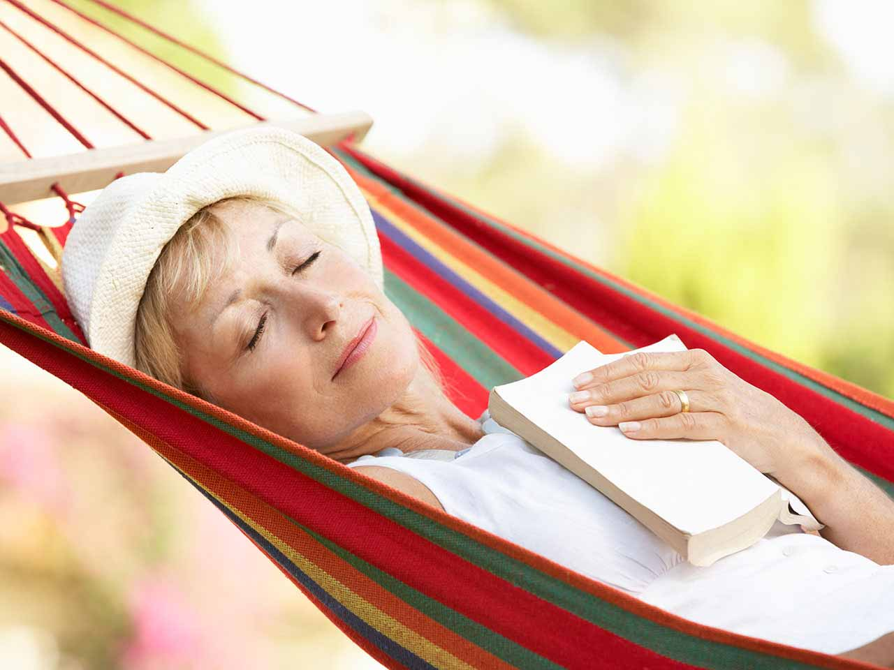Mature woman dozing in a hammock