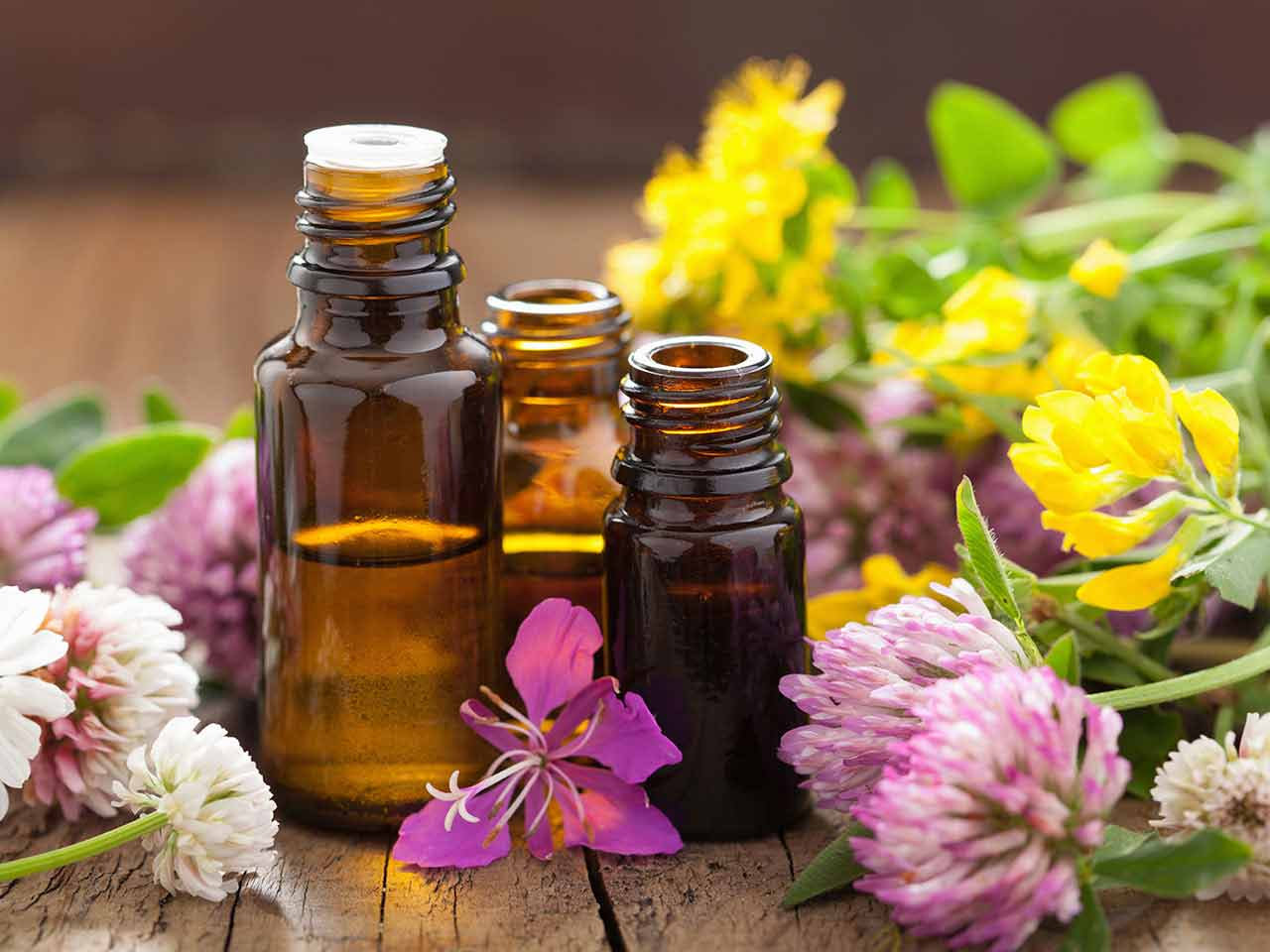 Essential oil bottles on wooden table with flowers
