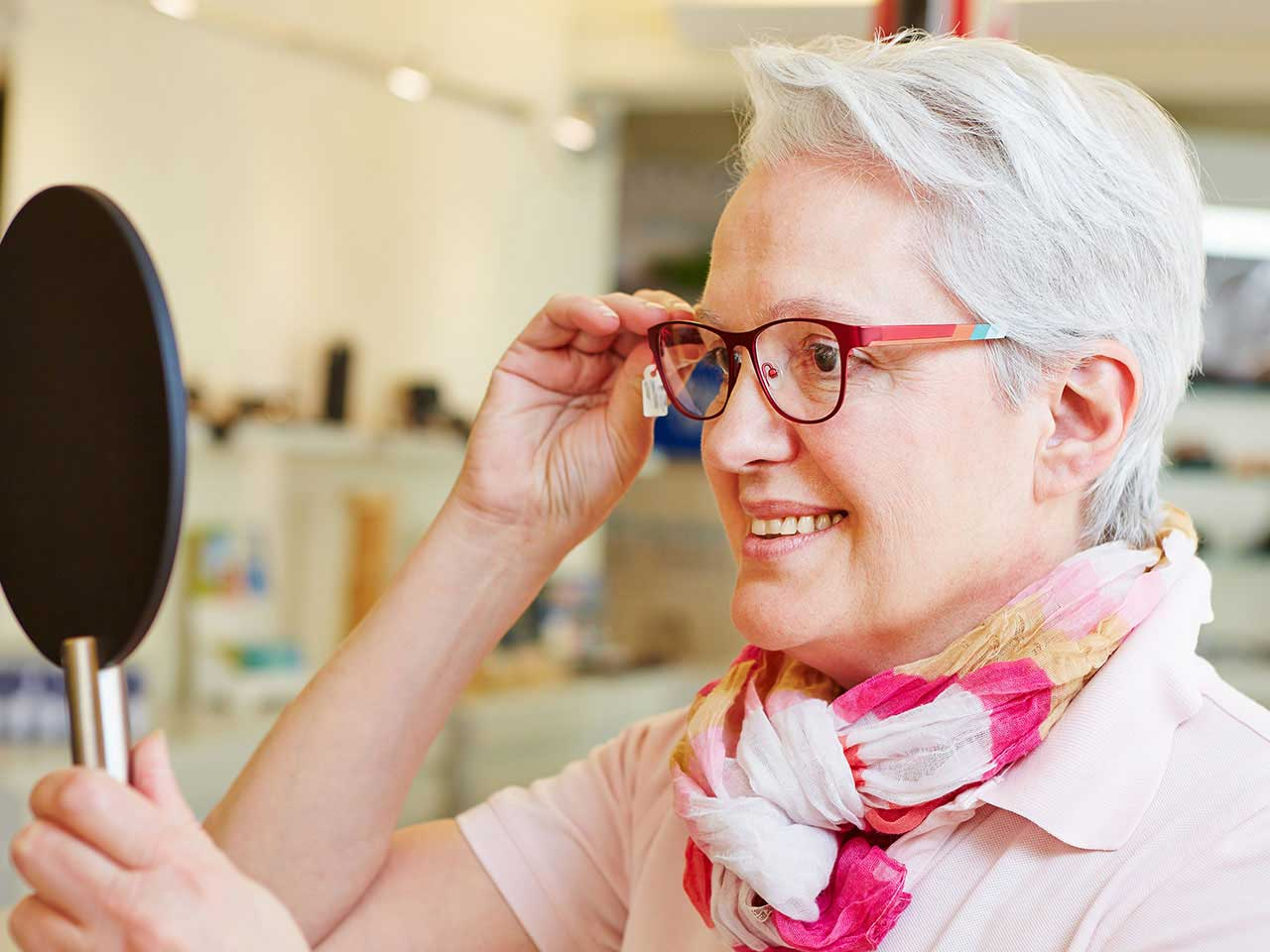 Senior lady trying on trendy glasses in opticians