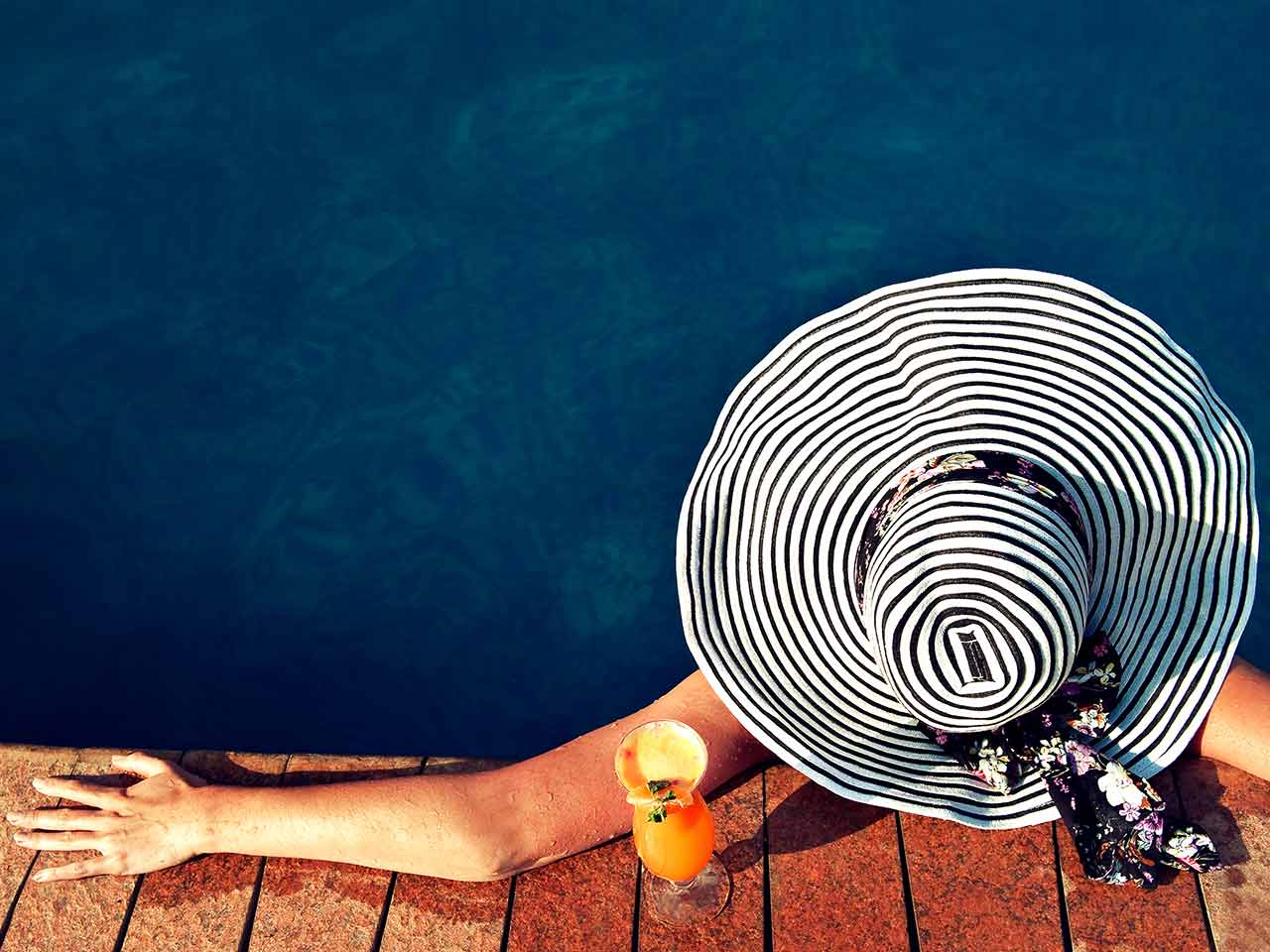 Woman relaxing in pool wearing sunhat