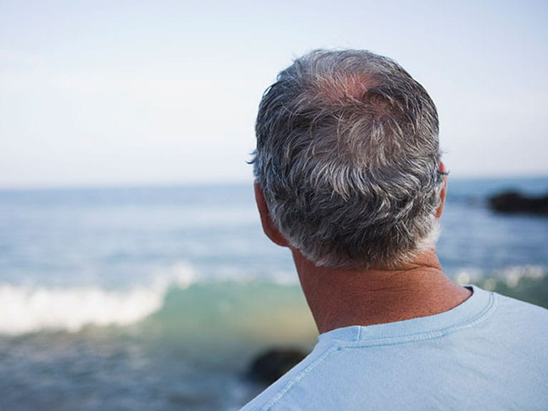 Middle-aged man looking out to sea