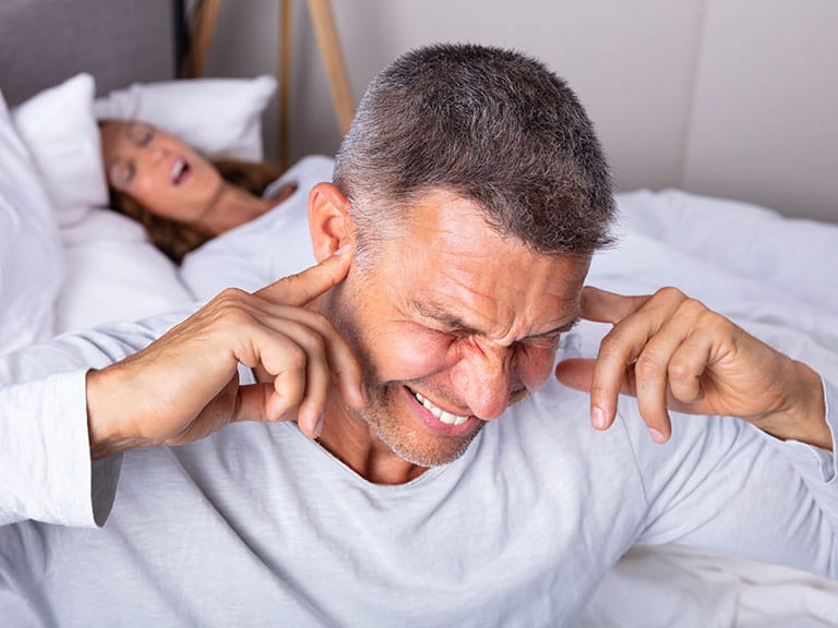A man is fed up with his wife's snoring