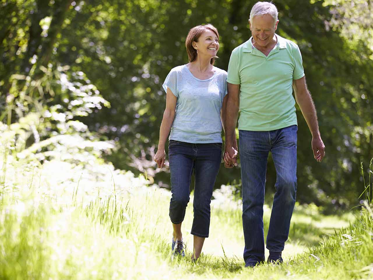 Mature couple laughing and walking in the sun