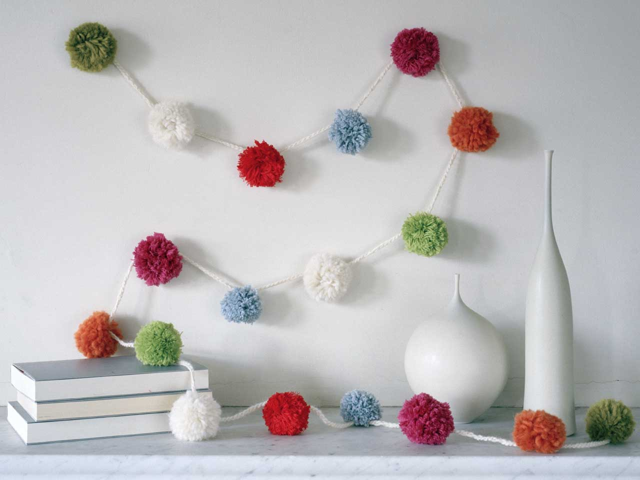 When you have enough pom poms you can make a garland by threading the pom poms together with ribbon or a crochet chain.