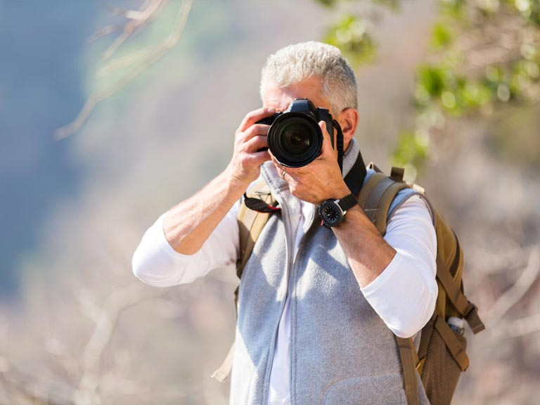 Mature man with DSLR