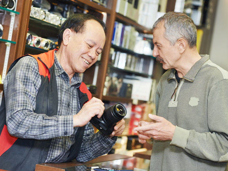 Man in shop buying camera