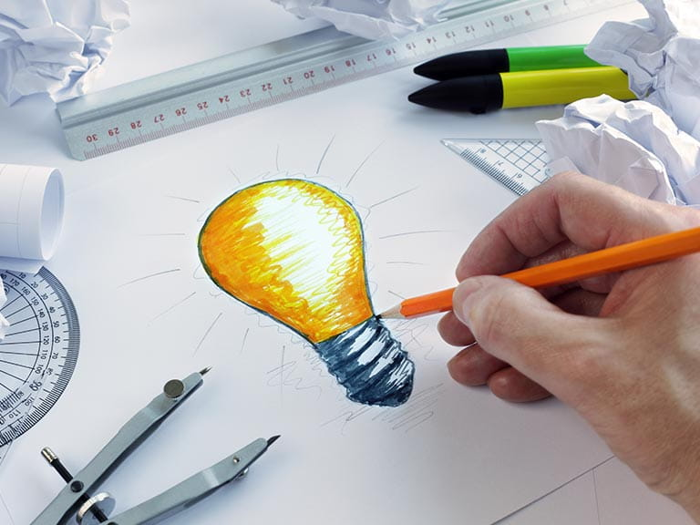 Hand drawing a light bulb