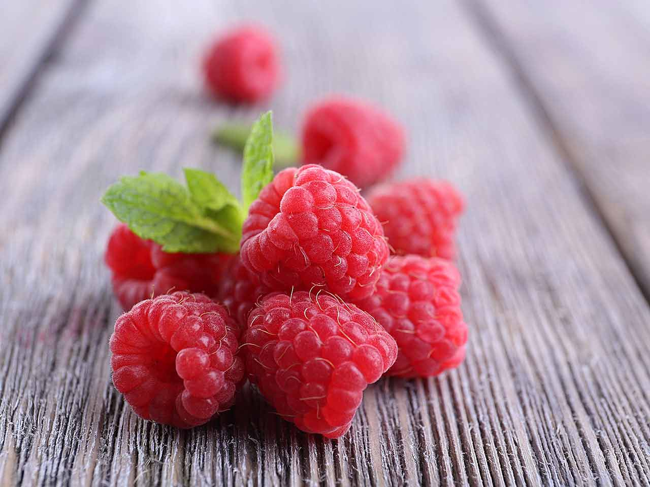 Close up of raspberries on wooden table