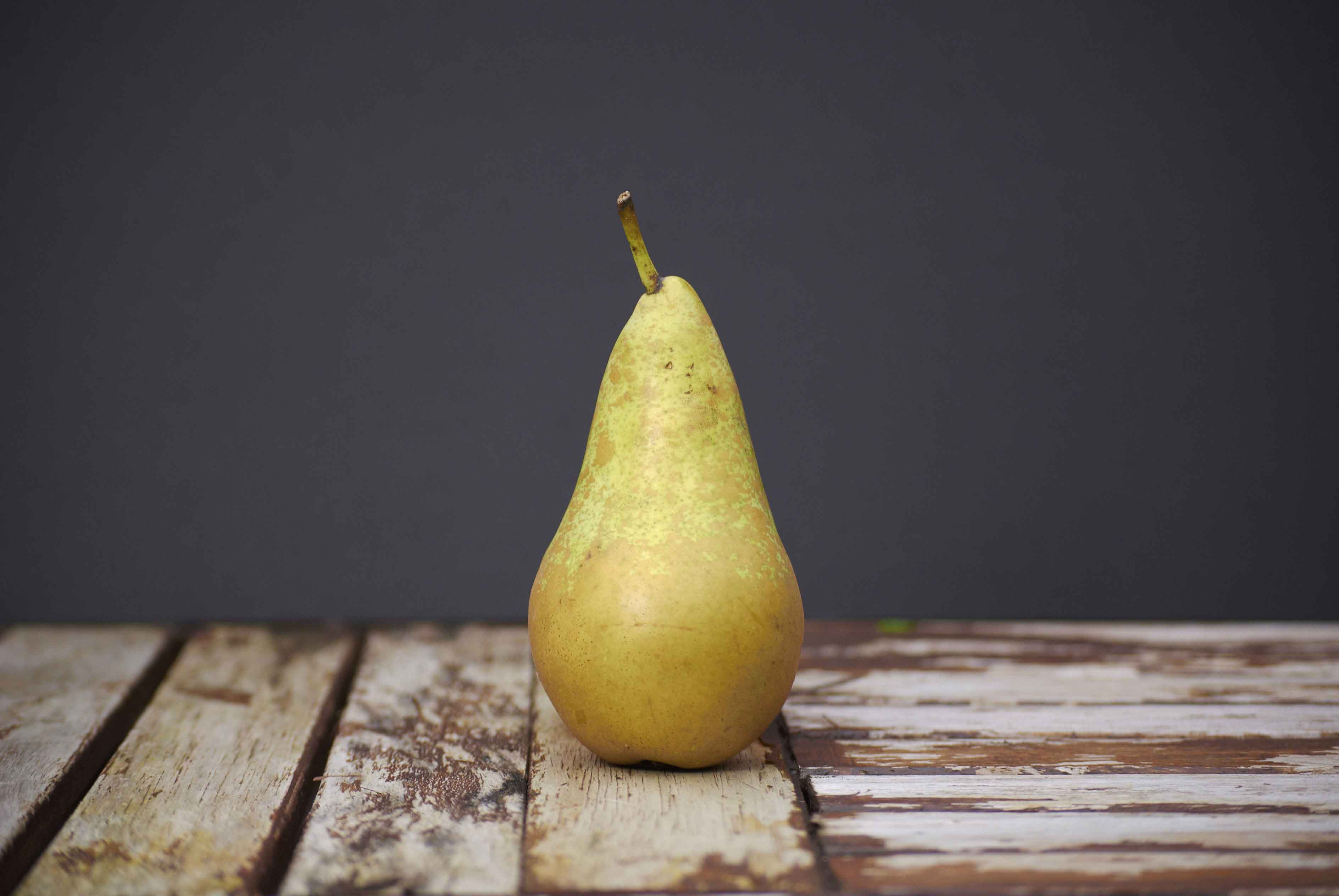 A pear sitting on a wooden board