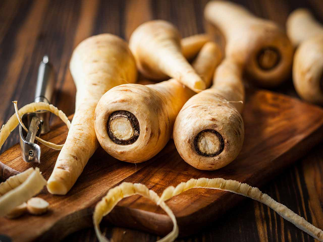 Raw parsnips on chopping board