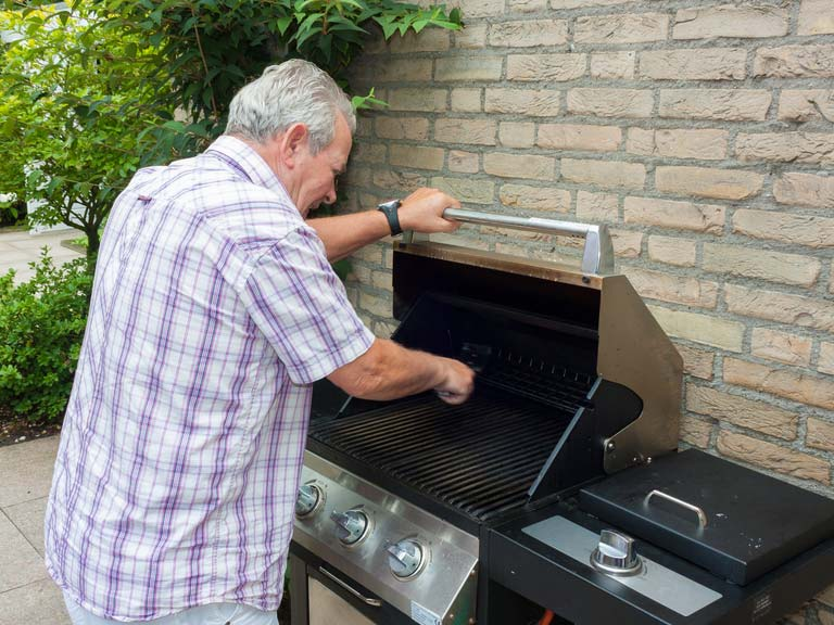 Man cleaning a BBQ